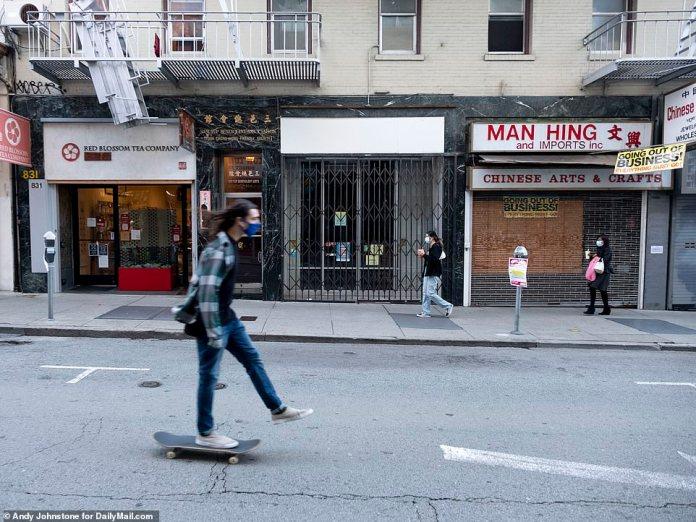 SAN FRANCISCO: Pedestrians walk past a rown of shut-up shops in San Francisco's Chinatown