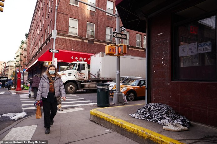 NEW YORK CITY:A person sleeps on a sidewalk in Chinatown in New York City in December