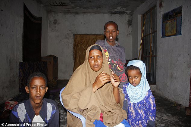 Fadumo Moalim Abdulle poses with 3 of her children, during an interview with the Associated Press in Mogadishu, Somalia, Monday, Jan, 18, 2021. The mother of eight has heard that her twenty year old son, Ahmed Ibrahim Jumaleh is one of the soldiers sent to Eritrea for military training in preparation to fight alongside Ethiopian troops. Pressure is growing on Somalia's government amid allegations that Somali soldiers have been sent to fight in neighboring Ethiopia's deadly Tigray conflict. Mothers have held rare protests in Somalia's capital, Mogadishu, and elsewhere, demanding to know the fate of their children who originally were sent to Eritrea for military training. (AP Photo/Farah Abdi Warsameh)