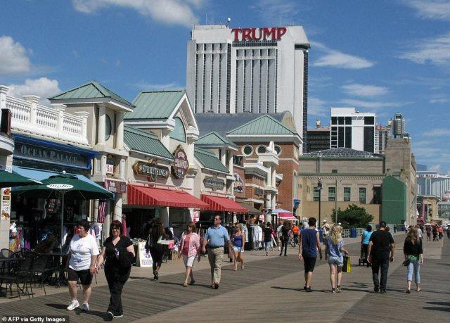 People walk on the boardwalk near the Trump Plaza Casino September 2014 in Atlantic City