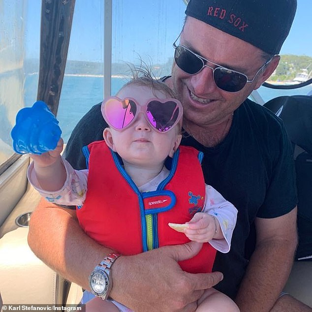 So cute!  Elsewhere during their family boat adventure, Karl uploaded a photo of himself sitting on the boat with Harper on his lap.