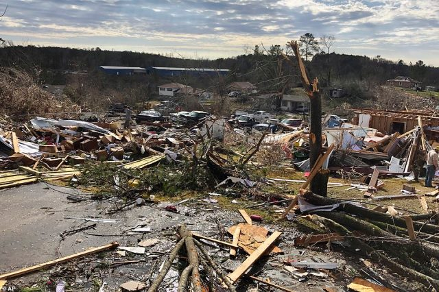 The trunk of a tree stands before the remains of homes that were all destroyed by the Fultondale tornado