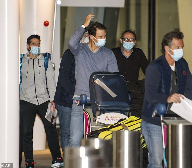 Nadal, pictured centre, arrives at Adelaide Airport ahead of the Australian Open on January 14. He has called on other players in quarantine ahead of the tournament to be grateful they were let into Australia at all