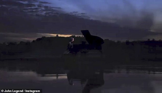 Taking the wheel: The multi-faceted singer is also seen playing the piano in the video as night falls on the water