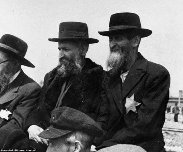 A group of Orthodox Jewish men - one of whom is wearing the makeshift star of David which Jews were forced to wear to distinguish them from other citizens - after arriving at Auschwitz-Birkenau in 1944. Soon after this picture was taken, the men would have been forced to give up their clothes, beards and hats