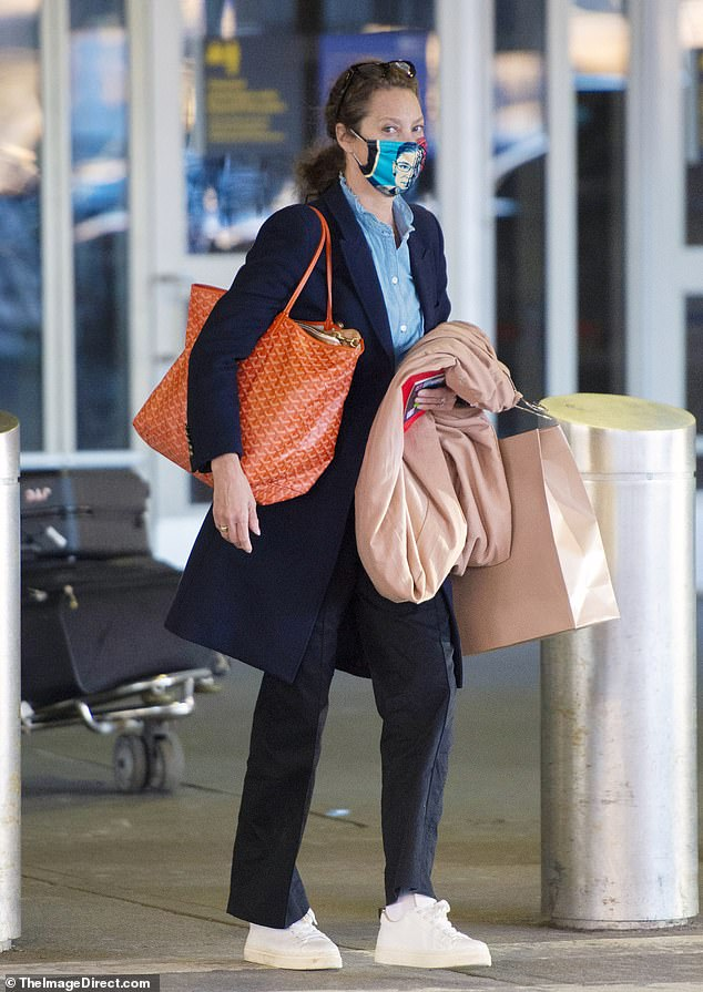 Chilled out for the long flight: At the airport, the Calvin Klein model had on a mid length black coat over a chambray shirt with dark slacks and white sneakers