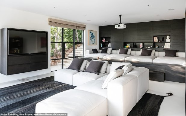 Movie night: a large screening room has black cabinets and shelves above a long lounge bench