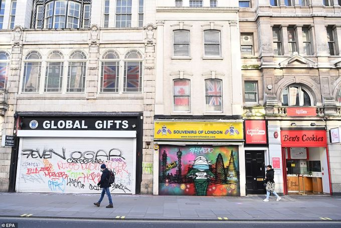 Pedestrians walk past closed shops on London's Oxford Street although a Ben's Cookies outlet (on the right) remains open