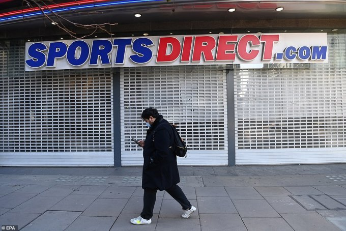 A man wearing a face mask walks past a closed Sports Direct shop on Oxford Street as non-essential stores remain closed