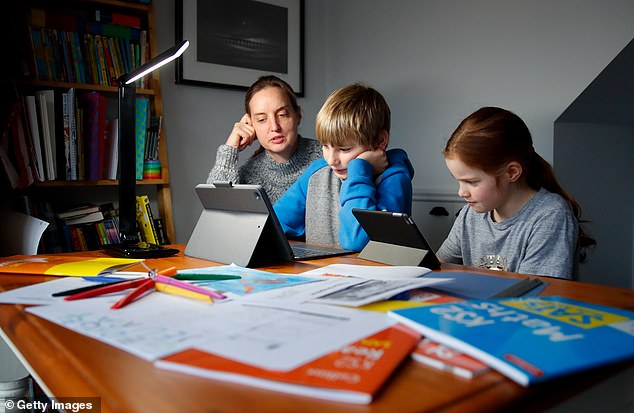 Oscar Mumby, 10, and Harriet Mumby, 8, are helped with their online schoolwork by their mother Jo Mumby in Cuckfield, West Sussex, last week as schools continue to be closed