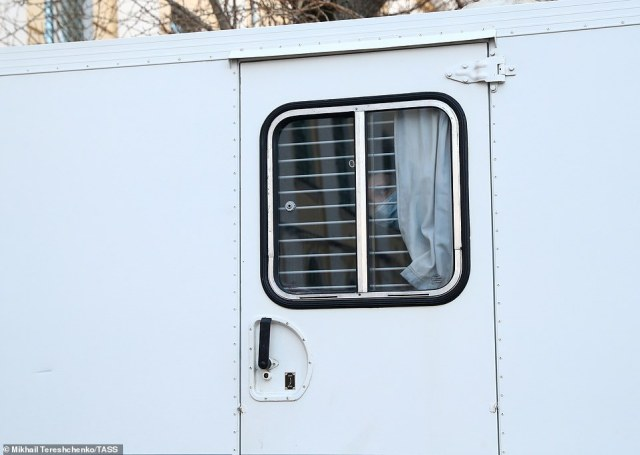 Navalny is seen through the bars of a prison van as he arrives at theSimonovsky District Court in Moscow