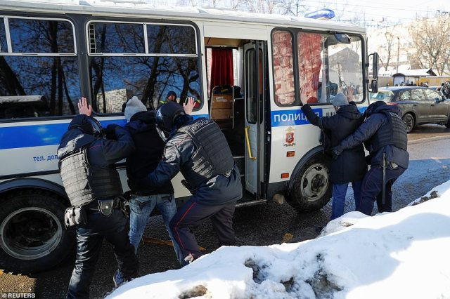 Navalny supporters are patted down before being loaded onto a waiting police bus