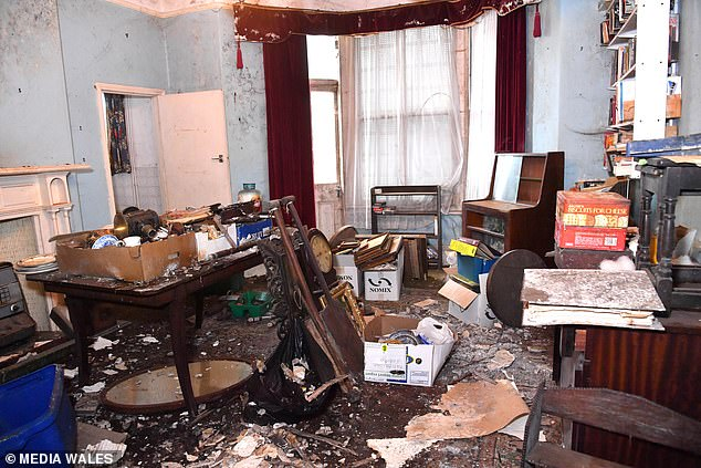The front reception room has a large bay window but the floor is covered in debris while the previous occupants' belongings remain