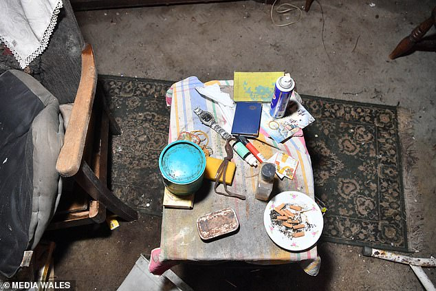 A coffee table packed full of items including an ashtray of cigarette ends looks frozen in time to the moment the owner left