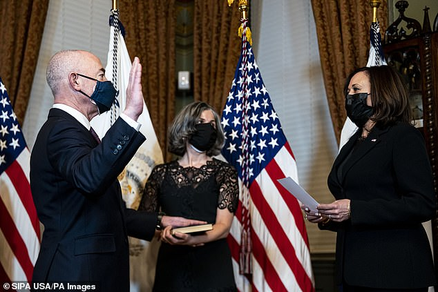 Department of Homeland Security Secretary Alejandro Mayorkas (left) is sworn-in Tuesday night by Vice President Kamala Harris (right)