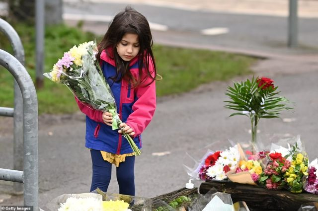 A young girl lays a floral tribute to Captain Tom outside his Bedfordshire home today. Amanda Holden has described how he became 'like a superhero' to youngsters