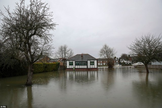 A house sits in flood water in Laleham Reach, Surrey, today after the banks of the River Thames burst