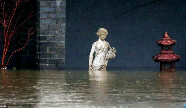 A statue outside a house which sits in flood water in Laleham Reach, Surrey, today after the banks of the River Thames burst