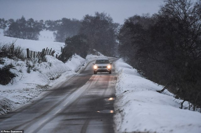 A car is seen driving through heavy snow near Dufftown in Scotland today as more flurries are expected in the coming days