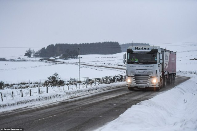 A lorry is seen driving through heavy snow near Dufftown in Scotland today with more blizzards on the way