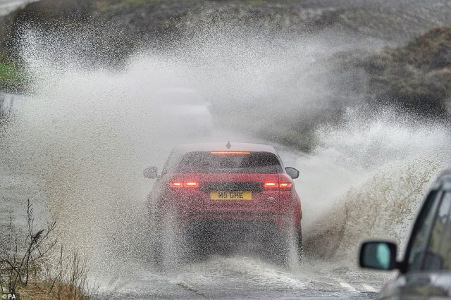 A cars goes through a flooded road at Seaton Delaval in Northumberland this afternoon following heavy rain