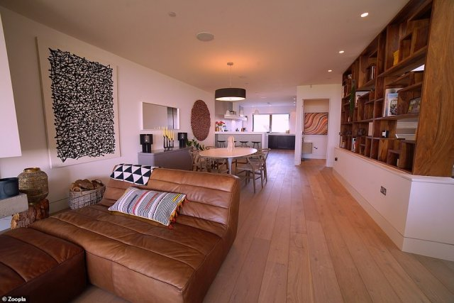 The modern home has a large open-plan living area with wooden flooring and lots of storage space