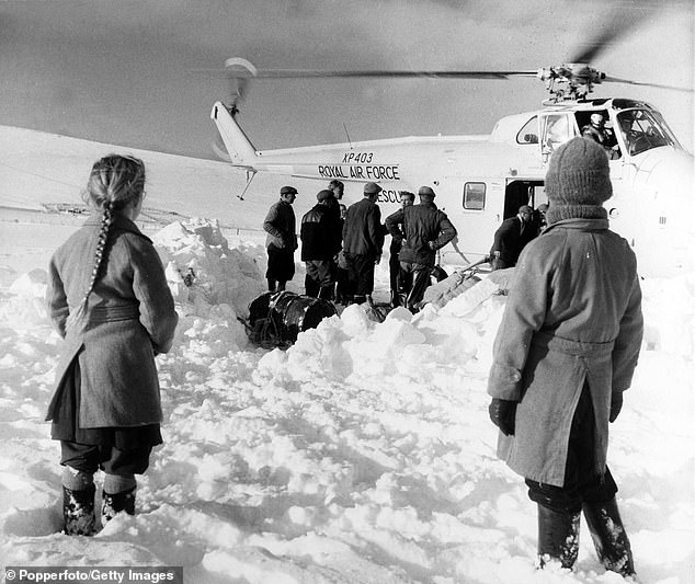Stranded families pictured cut off by deep snow in the Lammermuir Hills, Scotland, greet an RAF helicopter which was delivering supplies to isolated farms in January 1963