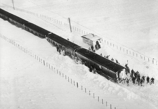 A gang of railway workers are seen digging out a train at Riccarton, five miles north of Newcastle, in the winter of 1962