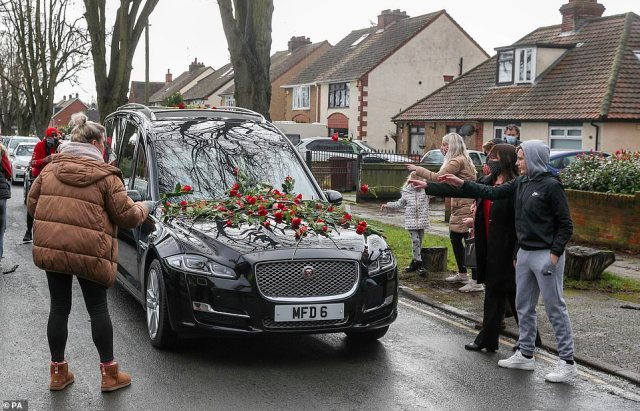 Members of the public place red roses on the hearse of Olly Stephens as the funeral procession slows at All Hallows Road, Reading