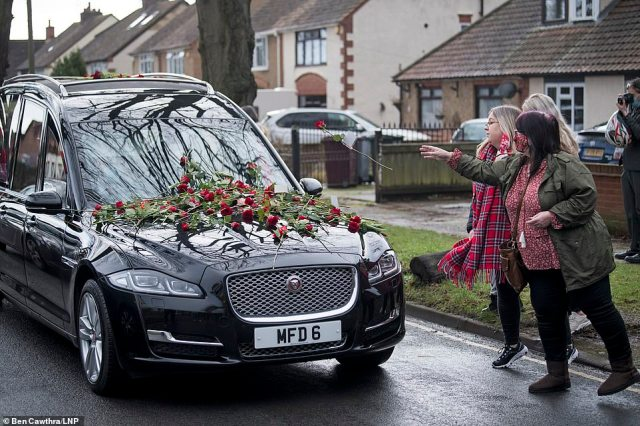 Members of the public wearing red throw red roses as the funeral procession carrying the coffin of teenager Olly Stephens arrives at Reading Crematorium