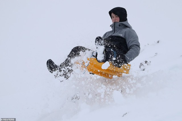 A boy sledges at Moulin Moor near Pitlochry as Storm Darcy approaches the country, in Scotland on Saturday