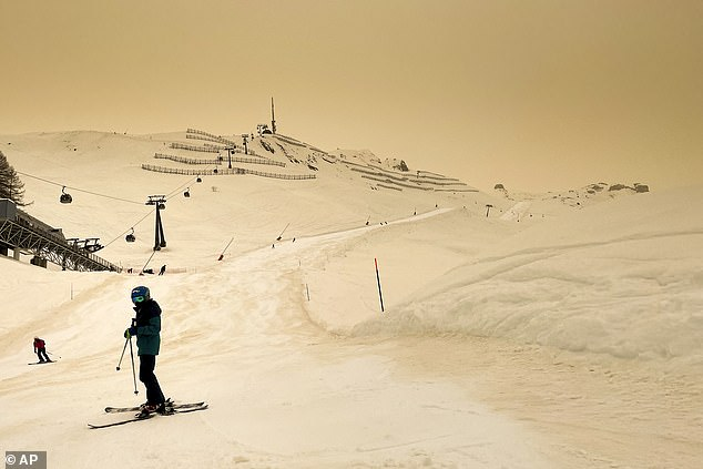 Skiers were seen taking to the slopes despite the freak weather incident after the increased concentration of dust from the African desert continued to stream in. Pictured: Anzere, Switzerland