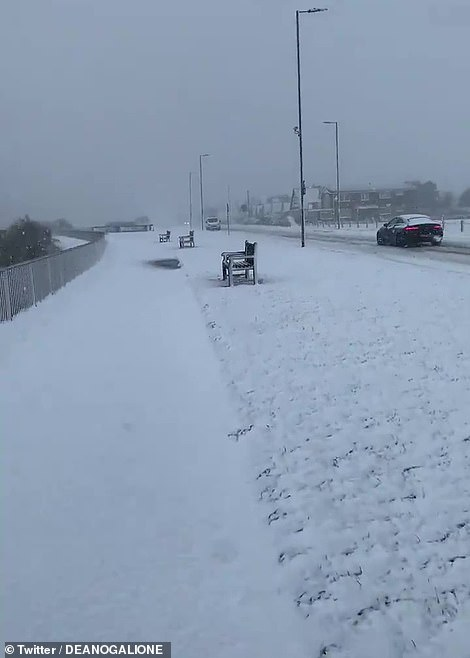 Pictured: Walkers trudging through the snow in Clacton-on-Sea, Essex after overnight snow as Storm Darcy strikes