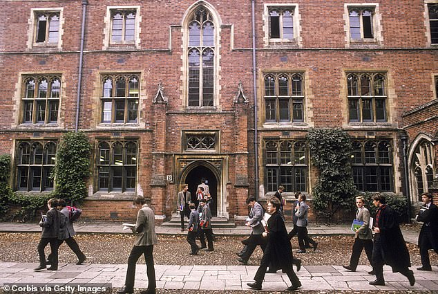 Tim Hands, master of Winchester College, said the Hampshire school hopes to produce 'leaders of the future' - which will be made up of both sexes from next year. Pictured, students walking to lessons