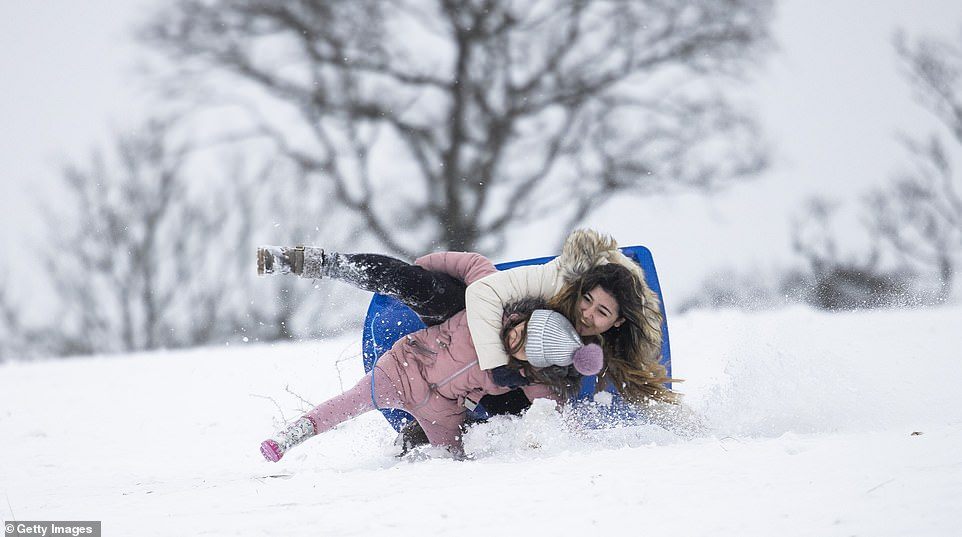 As large parts of the UK were hit with snow from Storm Darcy, some headteachers took it upon themselves to call a 'snow day' for home school students, scrapping online lessons and telling children to go out sledding instead (pictured: A child enjoys the snow at Farthing Common today)