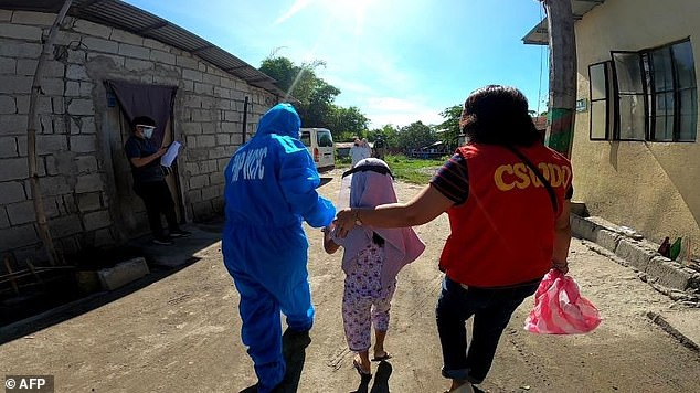 Filipino authorities walk a child out of the Angeles city home where abuse allegedly took place in her pyjamas and a face shield