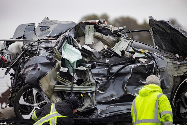 A crumbled car is seen being towed away from the crash site on Thursday afternoon. The scene took hours to clear