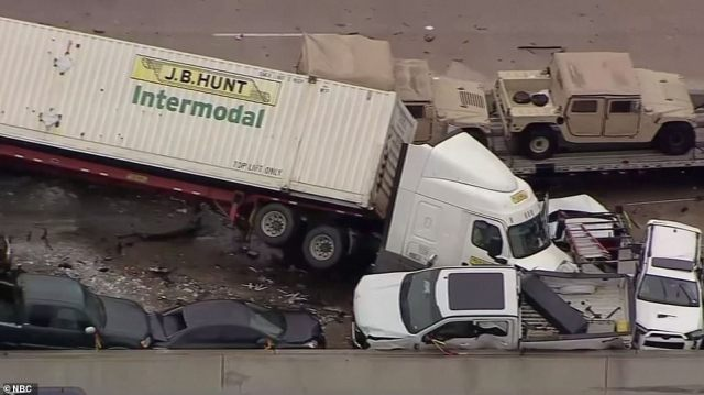 A huge truck that was flipped almost onto its side in the pile up. It pressed other, smaller vehicles up against the freeway barrier