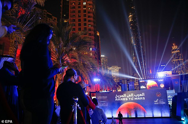 Pictured: People look to a big screen board displaying the arrival of the Hope Probe into Mars orbit at Burj Plaza — in front of the world's tallest building — in Dubai, United Arab Emirates