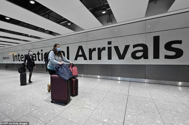 Travellers may have be forced to queue for up to five hours as the Government's quarantine hotels comes into force today. Pictured: Passengers arrive at Terminal 5 at Heathrow Airport