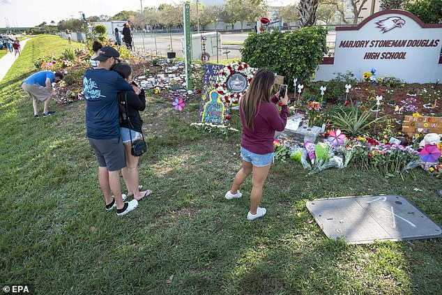 People stand in the makeshift memorial in front of the Marjory Stoneman Douglas High School in Parkland on the third anniversary of the shooting on Sunday. The confessed school shooter, Nikolas Cruz, who was 19 at the time, was armed with an AR-15-style rifle and fired between 100 and 150 rounds in a rampage that killed 14 students and three adult staff at the Marjory Stoneman Douglas High School