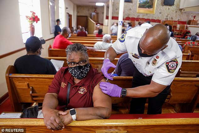 A woman receives the Pfizer-BioNTech COVID-19 vaccine from a Hillsborough County Fire Rescue paramedic Neil Brown at the historic Greater Bethel Missionary Baptist Church in Tampa, Florida, U.S. February 14, 2021