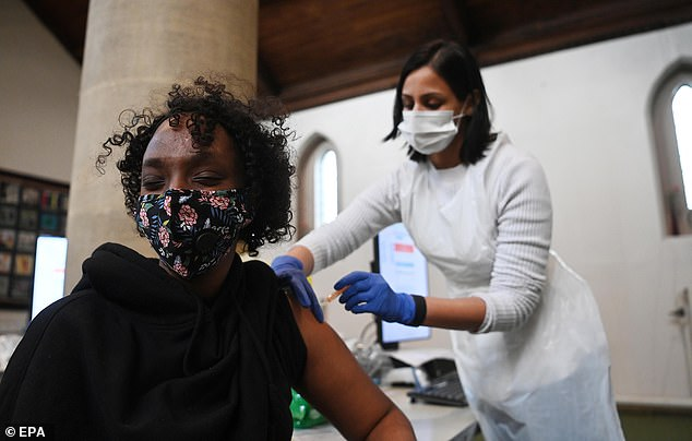 The joint committee on vaccination and immunisation (JCVI) will urge ministers to prioritise some ethnic minority groups, who are at a disproportionate risk of dying from Covid, Pictured: A woman gets a coronavirus vaccine in Ealing, West London