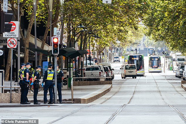 Police patrol Bourke St in Melbourne's CBD on Monday as cafes and retail shops are forced shut