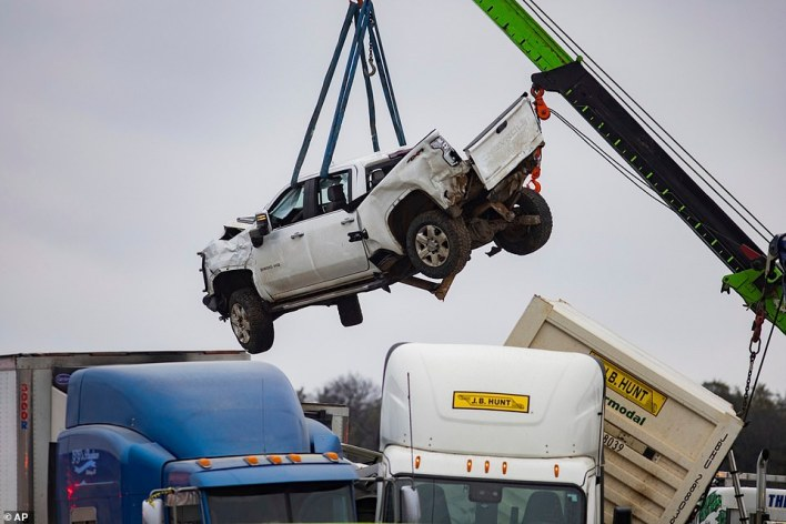 A crane is seen lifting out a damaged truck from the pile-up on Thursday afternoon