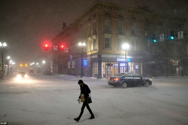 OHIO:A woman crosses Wooster Street as snow falls Monday night in Downtown Bowling Green