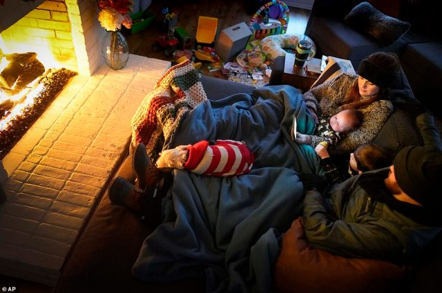 TEXAS:Dan Bryant and his wife Anna huddle by the fire with sons Benny, 3, and Sam, 12 weeks, along with their dog Joey, also wearing two doggie sweaters, with power out and temperatures dropping inside their home after a winter storm brought snow and freezing temperatures to North Texas