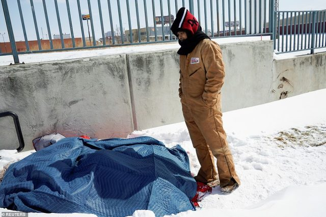 OKLAHOMA:Volunteer Salvador Cariaga checks on a man suffering from homelessness who has been sleeping on the ground under blankets during record breaking cold weather in Oklahoma City