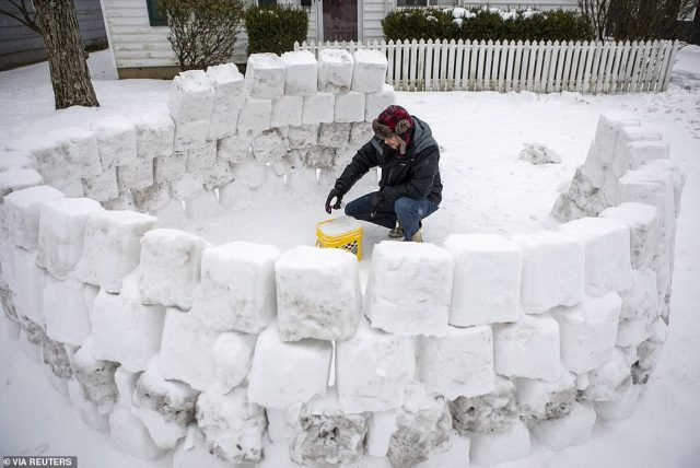 OHIO:Jeremy Seidt, 44, packs snow that he shoveled off his driveway into an empty cat litter bucket as he works on making an igloo in the front yard of his Sharon Township home in Columbus