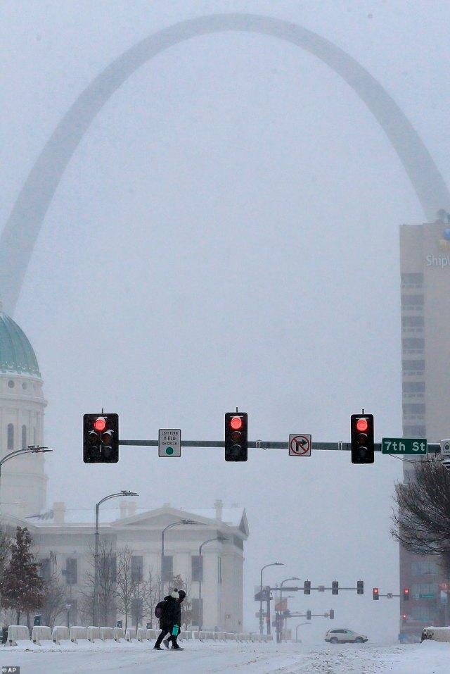 MISSOURI:Pedestrians cross Market Street during a snow storm in downtown St. Louis on Monday